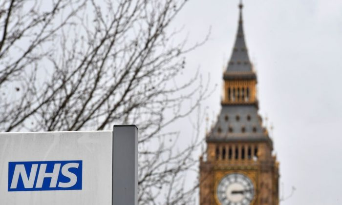 A NHS (National Health Service) sign is pictured outside St Thomas' Hospital, near the Houses of Parliament, in central London on March 8, 2017. Britain's economy will grow by 2.0 percent this year, sharply up on a previous forecast of 1.4 percent, finance minister Philip Hammond said Wednesday in his budget statement. Hammond also announced a two billion pound increase in spending for social care, over the next three years, in an effort to tackle pressure on the NHS. (BEN STANSALL/AFP/Getty Images)