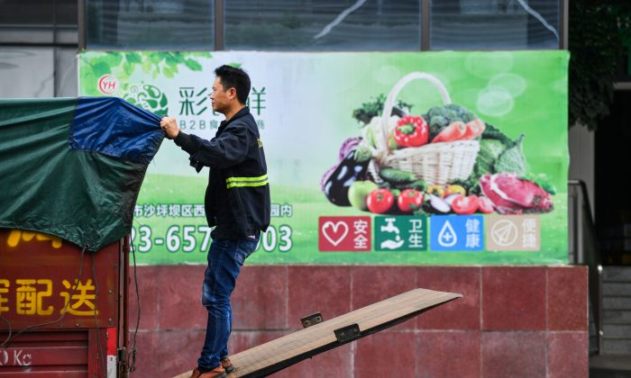 A worker adjusts a cover on the back of a truck outside a warehouse of Yonghui Superstores in Chongqing, China on Oct. 9, 2018. (Reuters)
