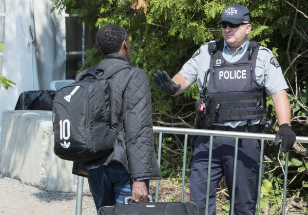An asylum seeker is confronted by an RCMP officer as he crosses the border into Canada from the United States on Aug. 21, 2017 near Champlain, N.Y. (The Canadian Press/Paul Chiasson)