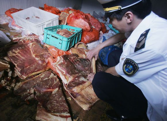 An officer with the Beijing Health Supervision Institute inspects spoiled pork at a freezer of the Huilongguan Chengbei Trade Market on July 28, 2005 in Changping County of Beijing, China. (China Photos/Getty Images)