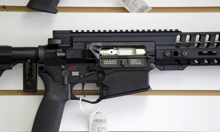 "A semi-automatic rifle, with ""God Bless America"" imprinted on it, is displayed for sale on the wall of a gun shop in Lynnwood, Wash., on Oct 2, 2018. (Elaine Thompson/AP)"
