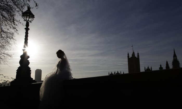 A bride sits on a wall opposite the Houses of Parliament during a wedding photo shoot in central London on Jan. 6, 2012. (Reuters/Stefan Wermuth)