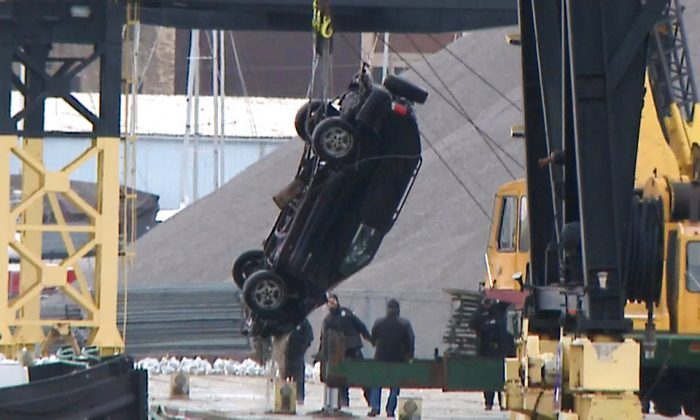 This Jan. 1, 2019 screen shot from WISN-TV shows authorities pulling out an SUV from the Kinnickinnic River, a day after it crashed into the river during a police chase. (WISN-TV via AP)