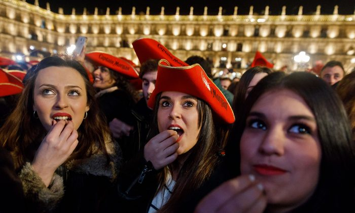 Students eat grape gummies while celebrating the traditional year-end party held in the main square of Salamanca, Spain on Dec. 15, 2016.  (Cesar Manso/AFP/Getty Images)