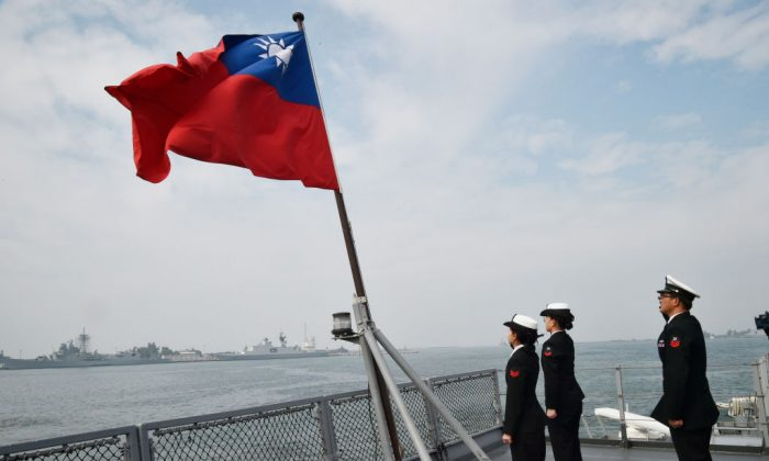 Taiwanese sailors salute the island's flag on the deck of the Panshih supply ship, at the Tsoying naval base in the southern Taiwanese city of Kaohsiung, on Jan. 31, 2018. (Mandy Cheng/AFP/Getty Images)