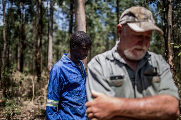 Farm worker Mogoala Justice Ratalele (L) stand near his employer Hans Bergmann after an incident in which he was held at gunpoint for the theft of the chainsaw that he was working with, on Nov. 2, 2017, in Tzaneen, South Africa. A long campaign of violence against the country's farmers, who are largely white, has inflamed political and racial tensions nearly a quarter-of-a-century after the fall of apartheid. (Gulshan Khan/AFP/Getty Images)