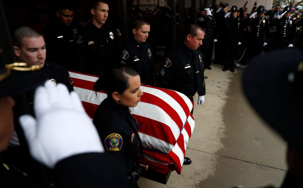Officers carry the flag-draped casket of slain officer Ronil Singh