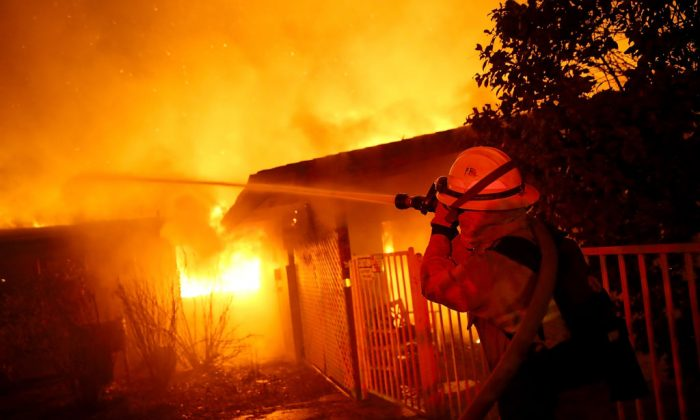Firefighters try to contain a fire so it doesn't spread to a neighboring building as the Camp Fire moves through the area on Nov. 8, 2018 in Paradise, Calif. ( Justin Sullivan/Getty Images)