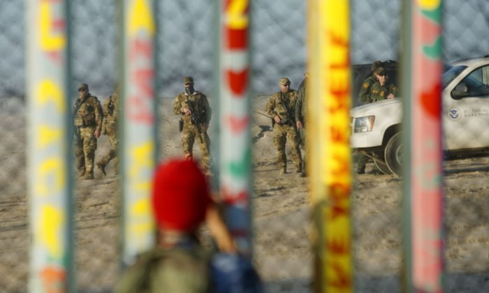 Border Patrol agents stand on patrol along the U.S.-Mexico border wall on Jan. 6, 2019 in Tijuana, Mexico. 