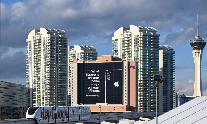 """A monorail train plastered with a Google advertisement passes a giant sign from Apple on a building as preparations are underway for the CES 2019 show, Jan. 6, 2019, in Las Vegas, Nevada.  Apple is taking a shot at rivals such as Google on the data privacy front with the message reading """"What happens on your iPhone stays on your iPhone.""""  (ROBYN BECK/AFP/Getty Images)"""