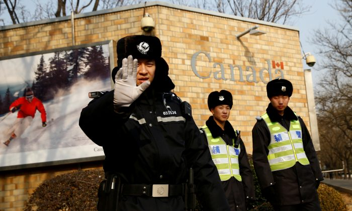 A police officer gestures at the photographer as security staff stand guard outside the Canadian embassy in Beijing, China, December 20, 2018.  (Reuters/Thomas Peter)