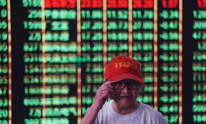 An investor stands in front of a screen displaying stock market figures at a securities company in Hangzhou in China's Zhejiang Province on June 19, 2018. (AFP/Getty Images)