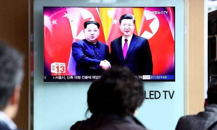 South Koreans watch a television broadcast reporting North Korean leader Kim Jong-un meeting with Chinese leader Xi Jinping at Seoul Railway Station in Seoul, South Korea on March 28, 2018.  (Chung Sung-Jun/Getty Images)