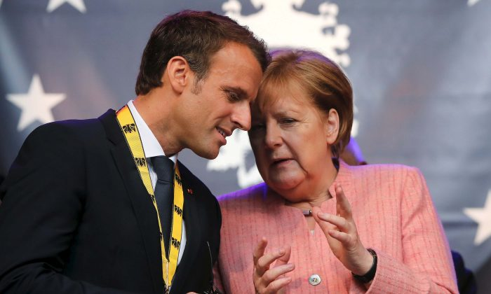 "French President Emmanuel Macron speaks with German Chancellor Angela Merkel after being awarded the Charlemagne Prize for ""European vision"" in Aachen, Germany, on May 10, 2018. (Reuters/Wolfgang Rattay/File Photo)"