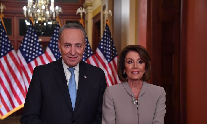 House Speaker Nancy Pelosi and Senate Democratic leader Chuck Schumer pose for pictures after delivering a response to President Donald Trump's televised address to the nation on border funding at the Capitol in Washington D.C. on Jan. 8, 2019. (NICHOLAS KAMM/AFP/Getty Images)