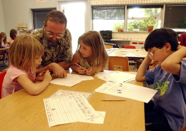 Substitute teacher, Andy  McCain, helps first grade students. BOULDER,CO. ON MAY 24TH 2004. (Andy Cross/The Denver Post via Getty Images)