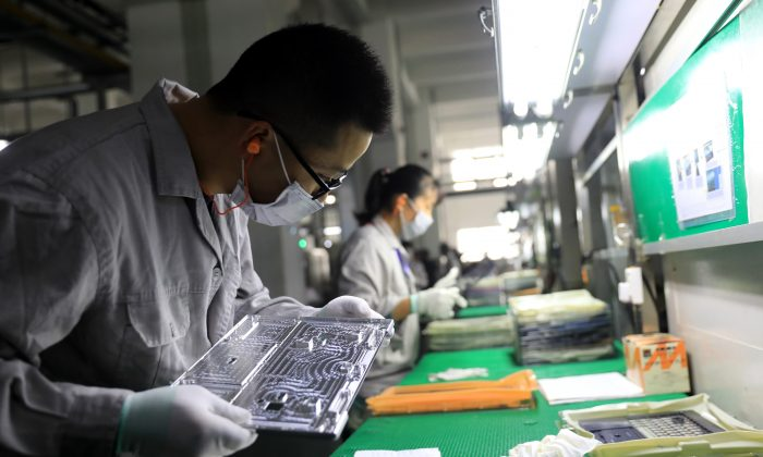 Workers check laptop parts in a factory in the Hangyong Auto Industrial Park, in Lu'an City, Anhui Province, China on Nov. 19, 2018. The factory produces equipment for Toshiba, Matsushita and other international brands. (STR/AFP/Getty Images)