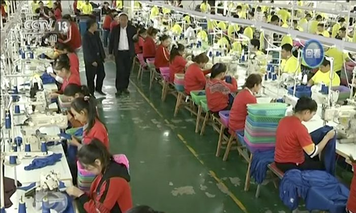 Muslim trainees work in a garment factory at the Hotan Vocational Education and Training Center in Hotan, Xinjiang, northwest China. A U.S. company that stocks college bookstores with t-shirts and other team apparel cut ties on Jan. 9, 2019, with a Chinese company that drew workers from an internment camp holding targeted members of ethnic minority groups. (CCTV via AP Video)