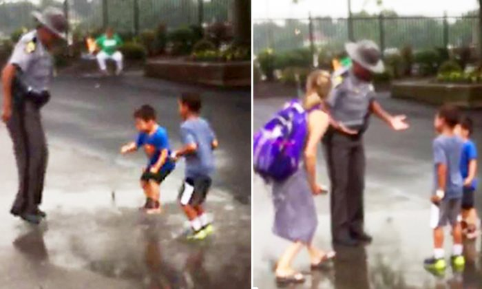 Ohio state trooper in Columbus, spotted having fun with two little boys jumping in a puddle, after heavy rains. (Facebook Video Screenshot | Ohio State Highway Patrol)