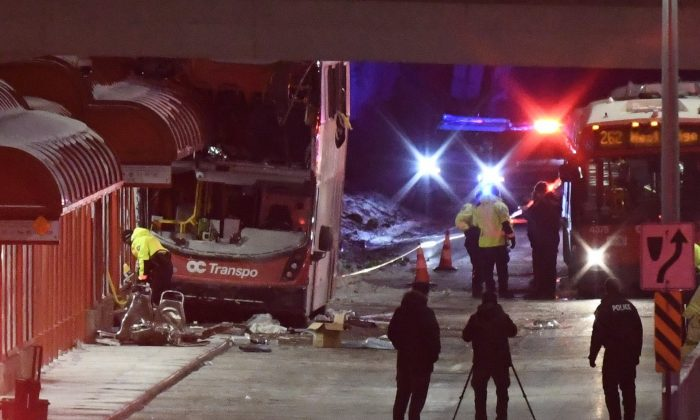Police and a first responders work at the scene where a double-decker city bus struck a transit shelter in Ottawa, on Jan. 11, 2019. (The Canadian Press/Justin Tang)