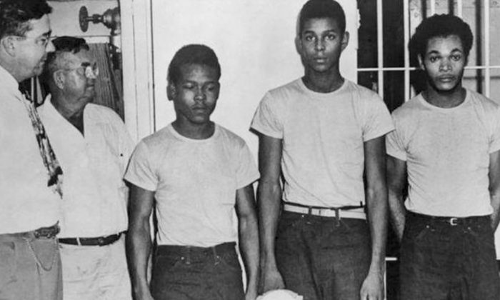 In this undated image released by the State Library and Archives of Florida, Lake County Sheriff Willis McCall, far left, and an unidentified man stand next to Walter Irvin, Samuel Shepherd and Charles Greenlee, from left, in Florida. (State Library and Archives of Florida/AP)