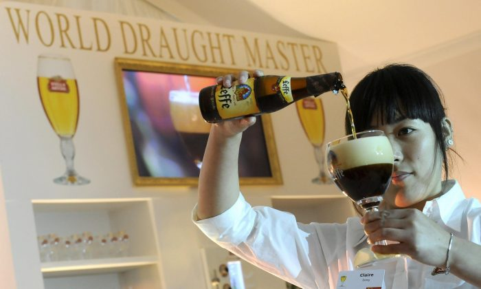 A contestant serves a Leffe beer during the Stella Artois World Draught Master 2008 on Oct. 29, 2008, in Leuven, Belgium. An alcohol-free version of world-famous Leffe brand is now available. (BENOIT DOPPAGNE/AFP/Getty Images)