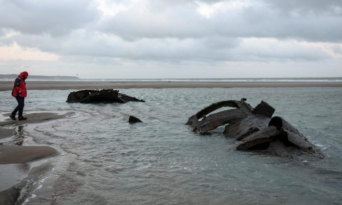 A man looks at the wreckage of a German submarine that ran aground off the coast of the city of Wissant in July 1917 and has recently resurfaced due to sand movements on the beach of Wissant, near Calais, northern France, on Jan. 9, 2019. (Denis Chalet/AFP/Getty Images)