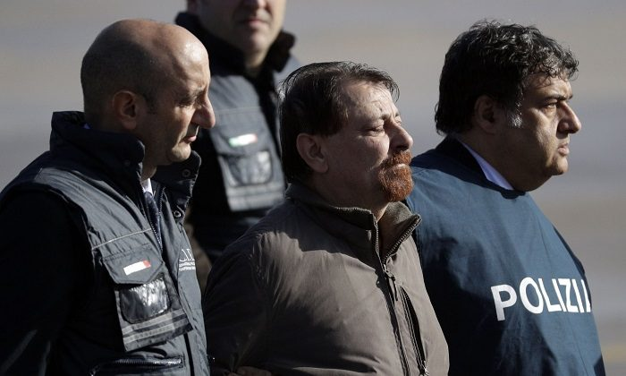 Italian fugitive Cesare Battisti arrives at Ciampino military airport, in Rome, on Jan. 14, 2019. Battisti a left-wing Italian militant who was convicted of murder three decades ago is heading home to serve a life sentence, after his life as a celebrity fugitive came to an abrupt end with his arrest in Bolivia by a team of Interpol agents. (Gregorio Borgia/AP Photo)