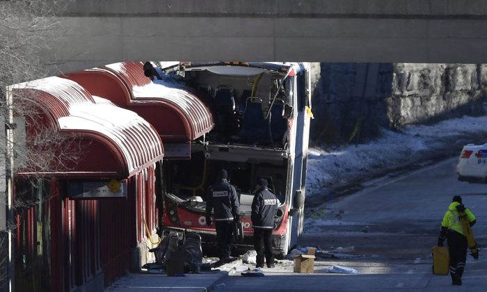 Transport Canada officials look at the scene where a double-decker city bus struck a transit shelter at the start of the afternoon rush hour on Jan. 11, at Westboro Station in Ottawa, on Jan. 12, 2019. (The Canadian Press/Justin Tang)