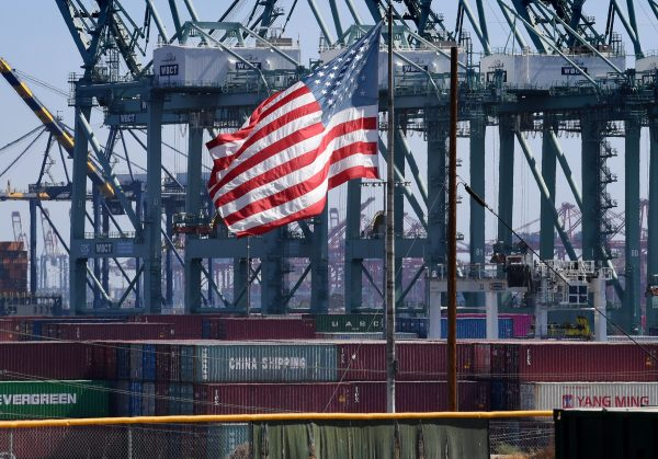 The US flag flies over Chinese shipping containers that were unloaded at the Port of Long Beach, in Los Angeles County