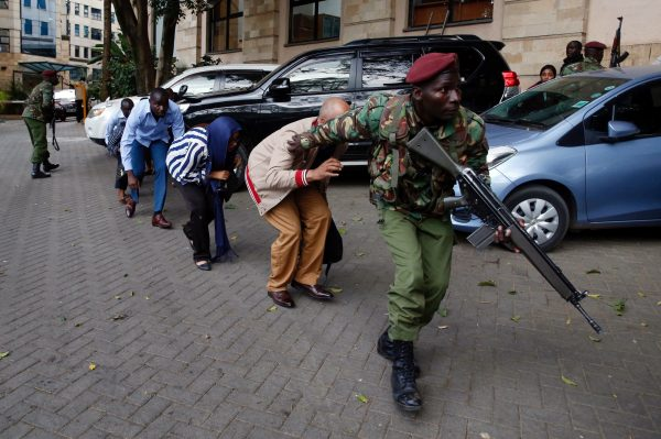 People are evacuated by a member of security forces at the scene where explosions and gunshots were heard at the Dusit hotel compound, in Nairobi, Kenya, Jan. 15, 2019. (Reuters/Baz Ratner)