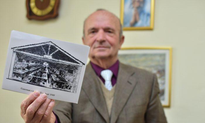 Simon Mirakaj holds the drawings from Tepelena camp in his office. (Antonio Çakshiri for The Epoch Times)