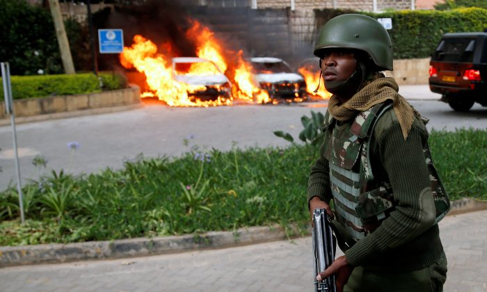 A policeman runs past burning cars at the scene where explosions and gunshots were heard at the Dusit D2 hotel compound, in Nairobi, Kenya, Jan. 15, 2019.  (Reuters Baz Ratner)