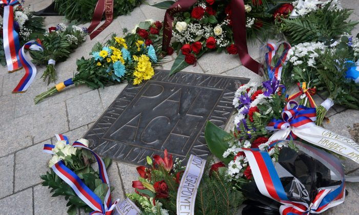 Flowers are placed next to a memorial plaque commemorating Jan Palach at Charles University in Prague, on Jan. 16, 2019. (Jiri Skacel/Reuters)