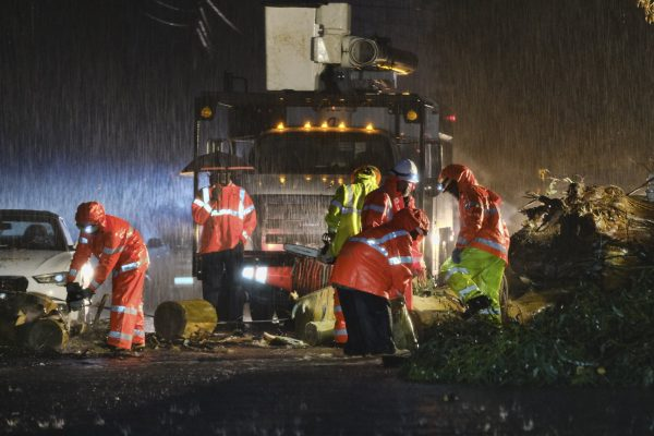 Department of Water and Power employees work in the pouring rain