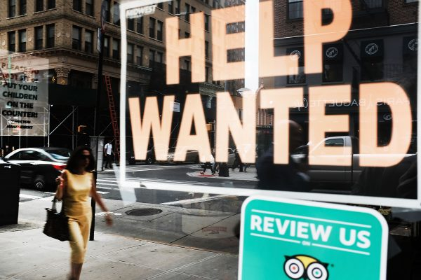A help wanted sign is displayed in the window of a Brooklyn business in New York