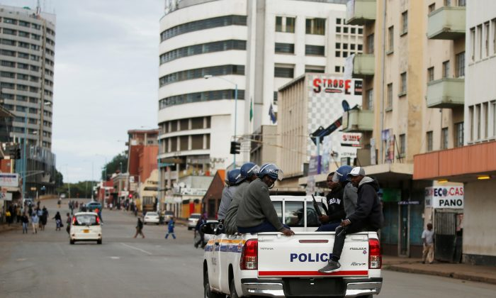 Zimbabwe Police officers are seen driving along the streets of Harare, Zimbabwe, on Jan. 17, 2019. (Reuters/Philimon Bulawayo)