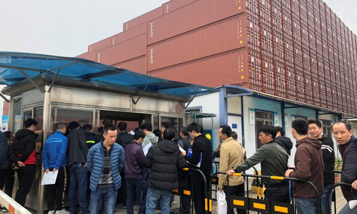 Workers queue to collect their employee contract termination letters at a Maersk container factory in Dongguan, Guangdong Province, China on Jan. 7, 2019. (Stella Qiu/Reuters)