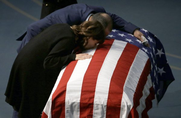 Lupe Corona and Merced Corona kiss the flag draped coffin of their daughter