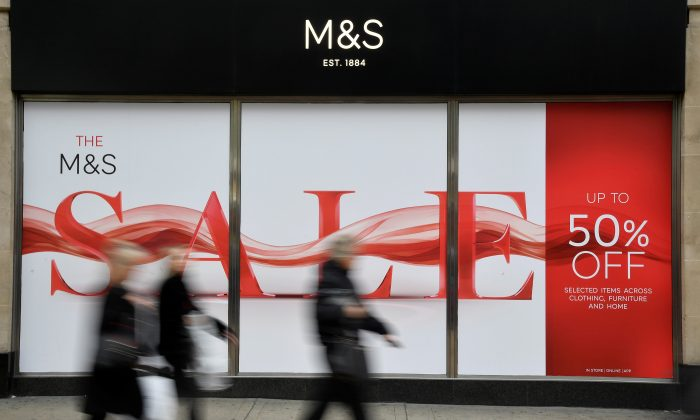 Shoppers walk past sale signs at a branch of the British clothing and food retailer Marks and Spencer on Oxford Street in London, Britain, on Jan. 3, 2019. (Toby Melville/Reuters)
