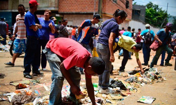 People look for food outside a looted supermarket at El Valle neighborhood, in Caracas, Venezuela, on April 21, 2017. (Ronaldo Schemidt/AFP/Getty Images)