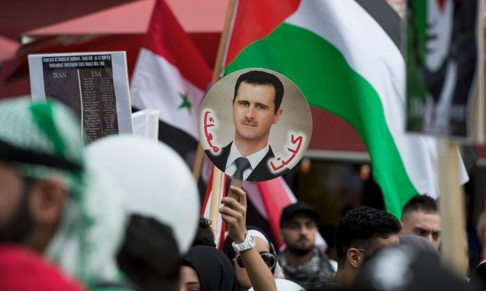 A demonstrator displays a placard featuring a portrait of Syrian President Bashar al-Assad during a rally in Berlin on Aug. 3, 2013. (John Macdougall/AFP/Getty Images)