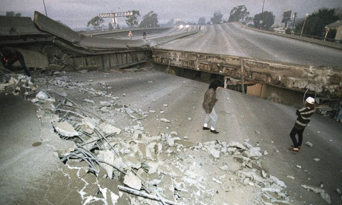 In this Jan. 17, 1994 file photo, Interstate 10, the Santa Monica Freeway, split and collapsed over La Cienega Boulevard following the Northridge quake in the predawn hours in Los Angeles. (AP Photo/Eric Draper)