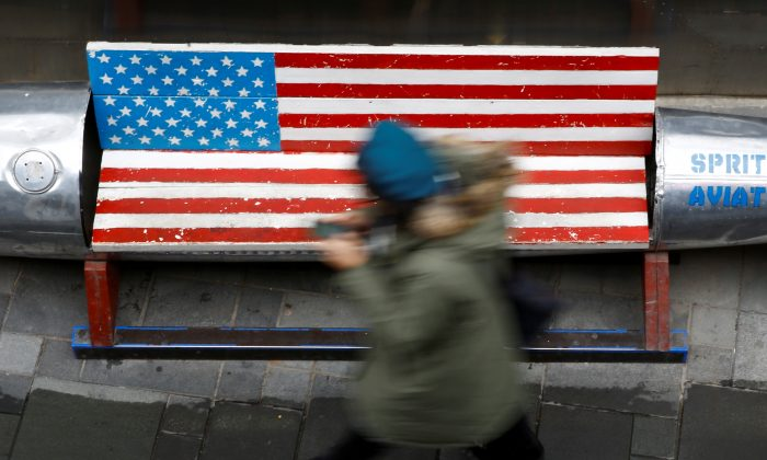 A woman walks past a bench painted in the colors of the U.S. flag outside a clothing store in Beijing on Jan. 7, 2019. (Thomas Peter/Reuters)