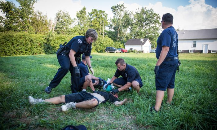 Local Police and paramedics help a man who is overdosing in the Drexel neighborhood of Dayton, Ohio, on Aug. 3, 2017. (Benjamin Chasteen/The Epoch Times)