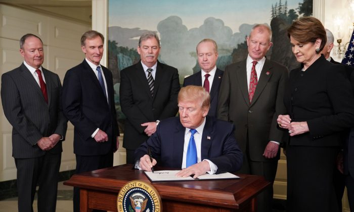 U.S. President Donald Trump signs trade sanctions against China in the Diplomatic Reception Room of the White House on March 22, 2018. (Mandel Ngan/AFP/Getty Images)