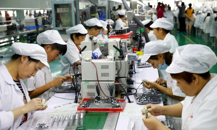 Employees work on a micro-motor production line at a factory in Huaibei City, Anhui Province, China, on June 23, 2018. (AFP/Getty Images)