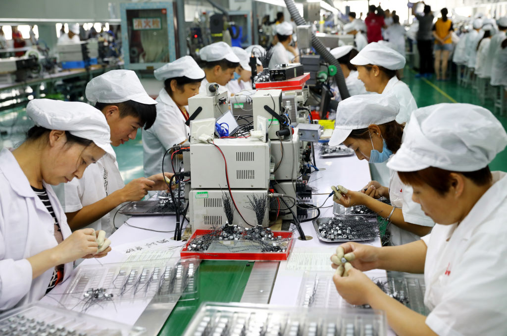 Employees work on a micro-motor production line at a factory in Huaibei City, Anhui Province, China.
