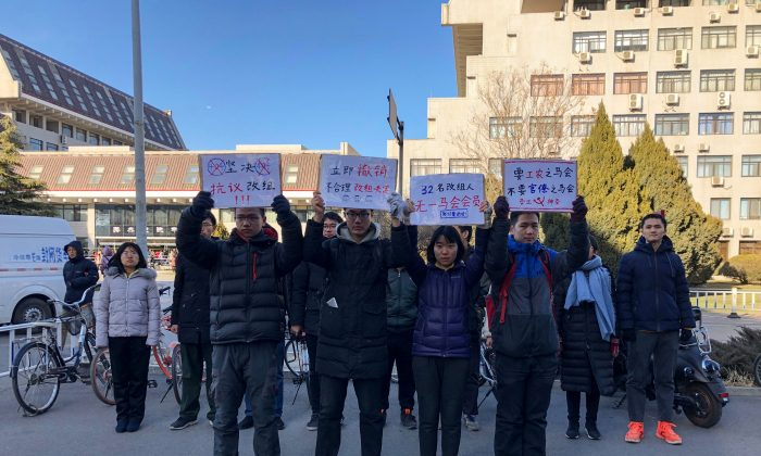 Four students hold up signs as they protest against the change in a student-run Marxist group's leadership at Peking University amid an ongoing crackdown on student activists in Beijing on Dec. 28, 2018. (Eva Xiao/AFP/Getty Images)