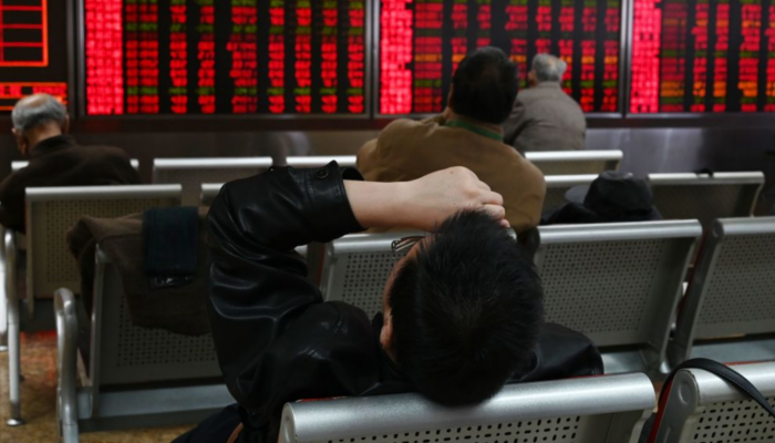 A man rests in front of screens showing stock prices at a securities company in Beijing on Jan. 21, 2019. (GREG BAKER/AFP/Getty Images)
